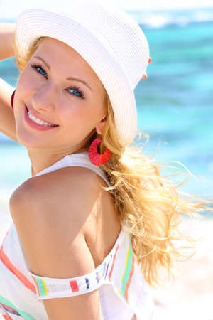Attractive blond woman standing by the sea photo