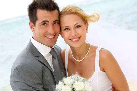 young couple smiling: Cheerful married couple standing on the beach Stock Photo