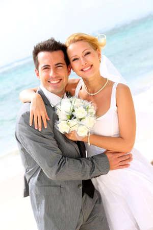 boda en la playa: De pie alegre pareja de casados ??en la playa