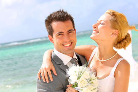 blonde couple: Cheerful married couple standing on the beach Stock Photo