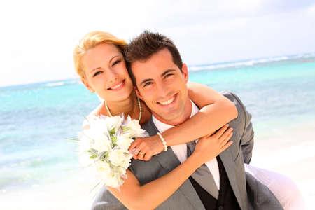 Groom holding bride on his back Standard-Bild