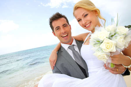 Groom holding bride in his arms at the beach photo