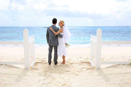 Just married couple standing by a fence towards this ocean photo