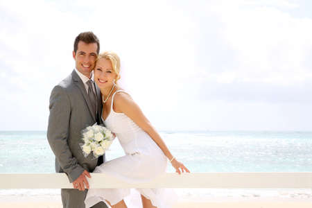 textspace: Bride and groom sitting on a fence by the beach Stock Photo