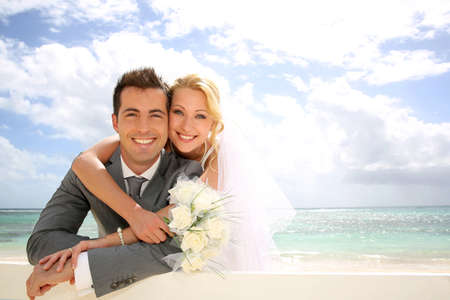 Just married couple leaning on fence by the beach photo