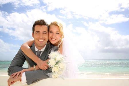 Net getrouwd paar leunend op hek aan het strand