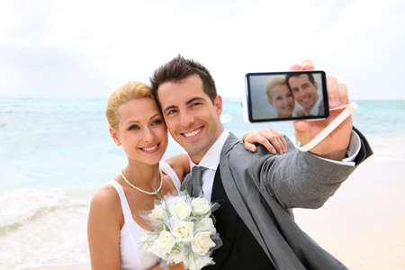 taking photo: Bride and groom taking picture of themselves