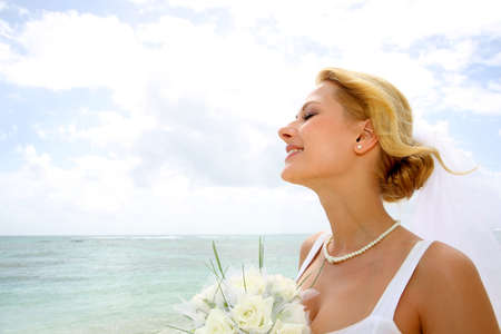Portrait of beautiful bride with eyes shut by the beach photo