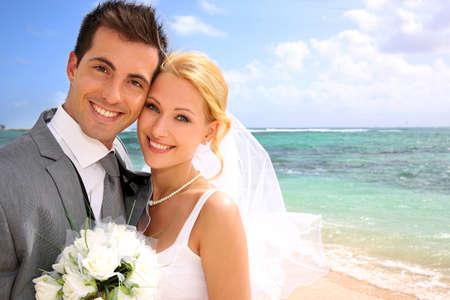 luna de miel: Retrato de la hermosa novia y el novio en la playa