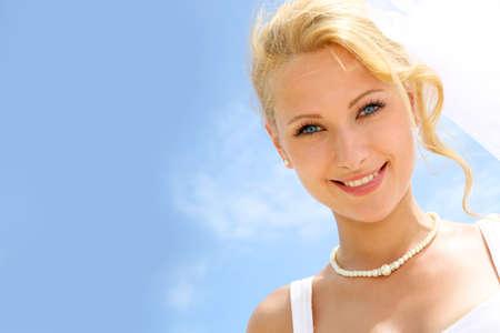 rubia ojos azules: Retrato de la novia hermosa con el cielo azul en el fondo