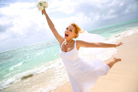 whiteness: Cheerful bride showing happiness at the beach Stock Photo