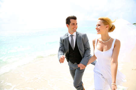 Just married couple running on a sandy beach photo