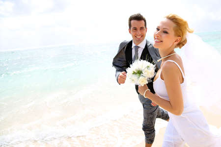 woman beach dress: Just married couple running on a sandy beach