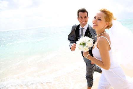 recien casados: Just married pareja que se ejecuta en una playa de arena