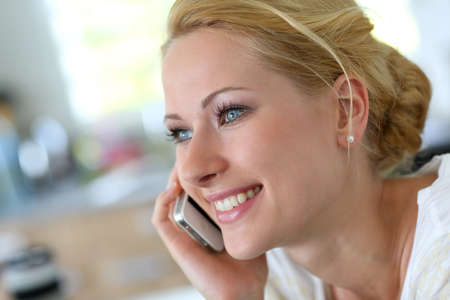 Attractive blond woman at home talking on mobilephone photo