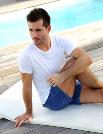Young man doing stretching exercises on pool deck photo