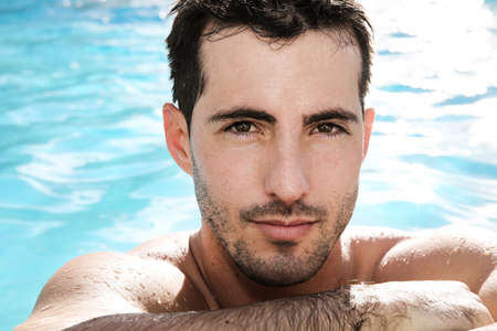 Portrait of handsome guy in swimming-pool photo