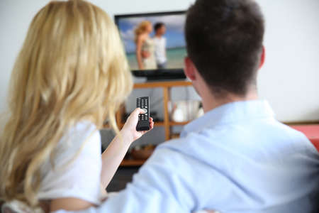 woman watching tv: Back view of couple choosing tv program