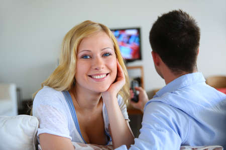 Smiling blond girl watching tv with boyfriend photo