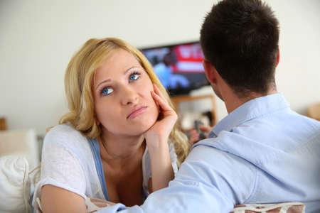 sad women: Blond woman being bored watching tv ith boyfriend