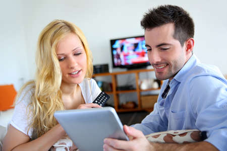 tv set: Young couple choosing tv program on internet Stock Photo