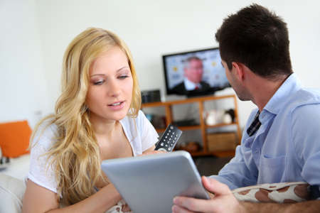 woman watching tv: Young couple choosing tv program on internet Stock Photo