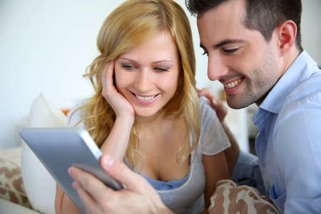 Cheerful couple websurfing with digital tablet at home photo