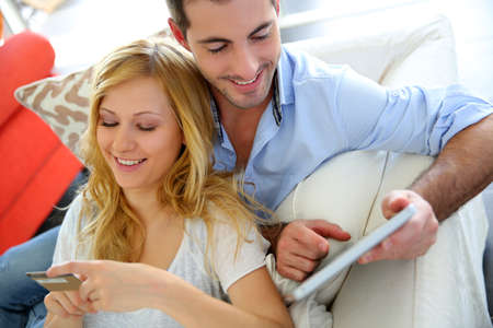 Cheerful young couple doing online shopping with tablet photo