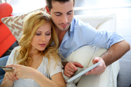 shopping online: Cheerful young couple doing online shopping with tablet