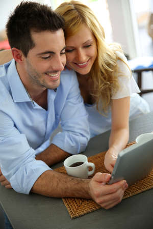 Young couple websurfing with tablet in home kitchen photo
