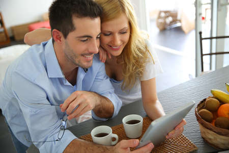 eye pad: Young couple websurfing with tablet in home kitchen Stock Photo