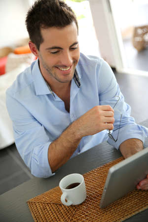 Cheerful young man websurfing on digital tablet at home photo
