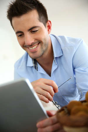 Cheerful young man websurfing on digital tablet at home Stock Photo - 17184066