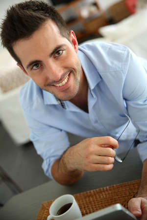 Cheerful young man websurfing on digital tablet at home Stock Photo - 17184031