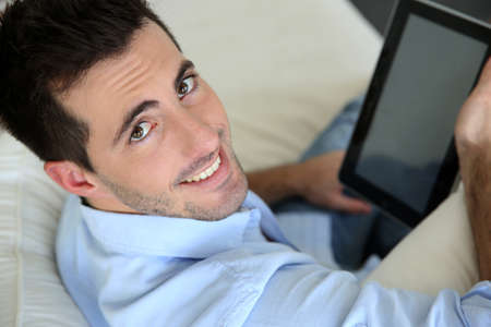 Man sitting in sofa using electronic tablet photo