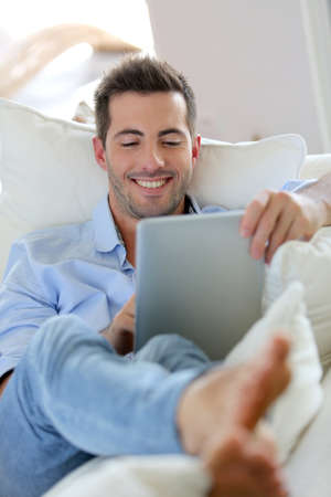 Cheerful young man laying in sofa with digital tablet photo