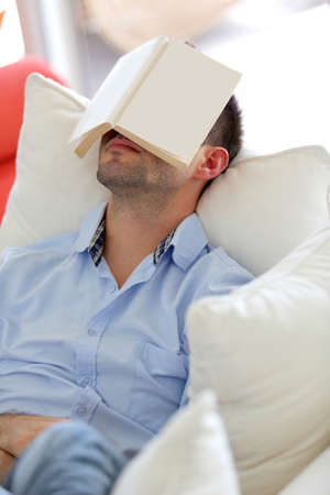 Young man sleeping in sofa with book covering his face photo
