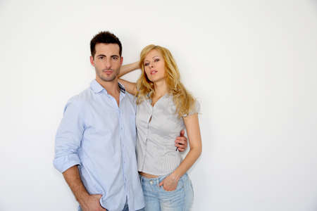 Trendy young couple standing on white background photo