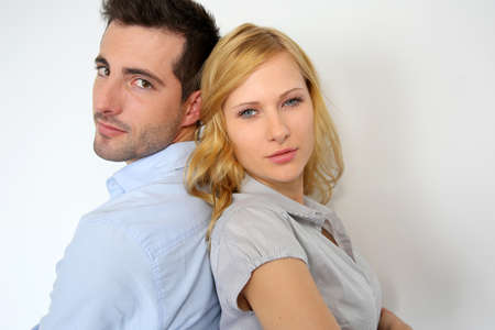 serious guy: Couple standing back to back on white background Stock Photo