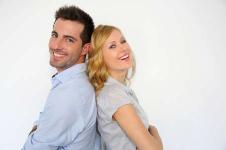 Cheerful couple standing back to back on white background photo