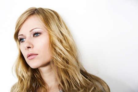 blonde yeux bleus: Gros plan d'une femme blonde sur fond blanc
