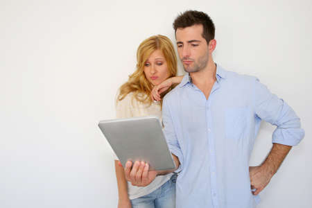 Couple looking at tablet screen with puzzled look Stock Photo - 17184138