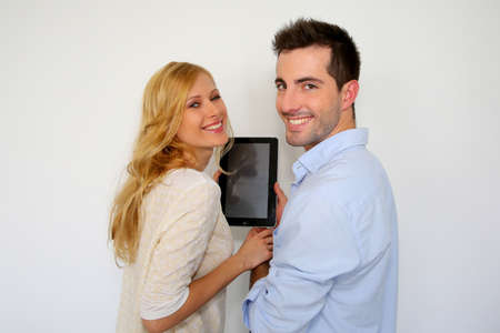 Couple standing on white background with tablet photo