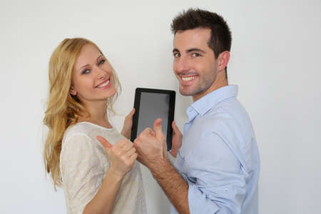 Cheerful couple with tablet showing thumbs up photo