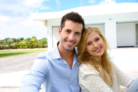 Cheerful young couple sitting in front of modern house photo