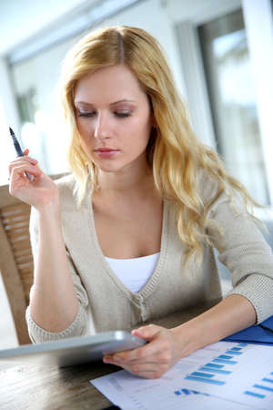 telephone saleswoman: Woman working from home with smartphone and tablet