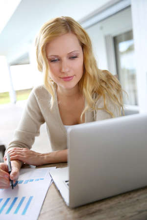 saleswomen: Smiling woman working from home on laptop