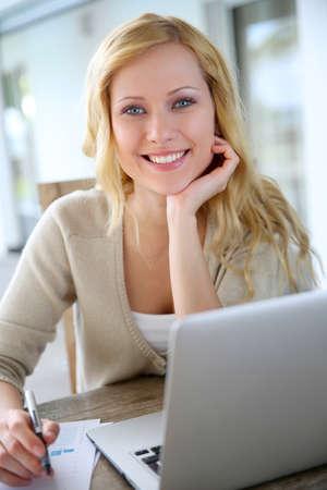 dolgozó: Mosolygó nő otthon dolgozik a laptop Stock fotó