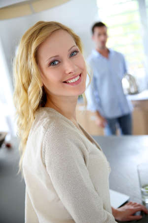 woman standing: Blond woman standing in kitchen, man in background Stock Photo