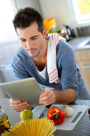 Closeup of smiling man in kitchen using tablet photo